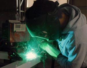 Homme réalisant des travaux de soudure pour fabrication d'enseigne - fabricant d'enseignes et de signalétiques